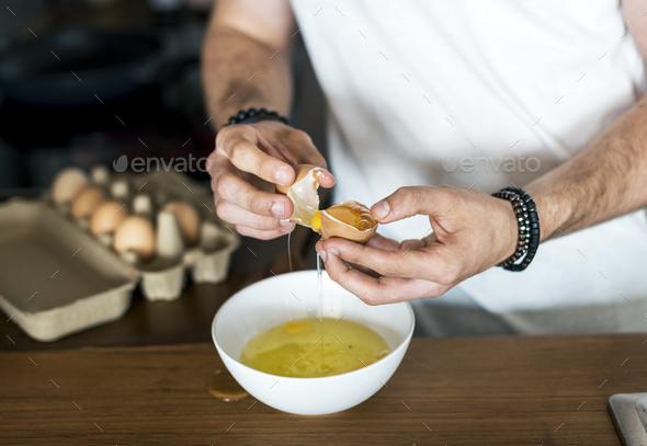 Closeup of man separating egg yolk - Stock Photo - Images