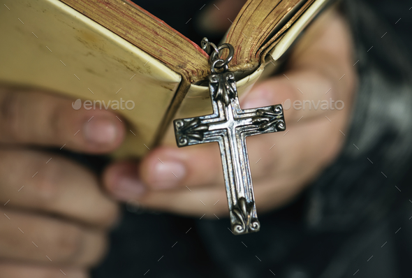Close up of a man reading a bible with cross hanging religion and belief concept - Stock Photo - Images