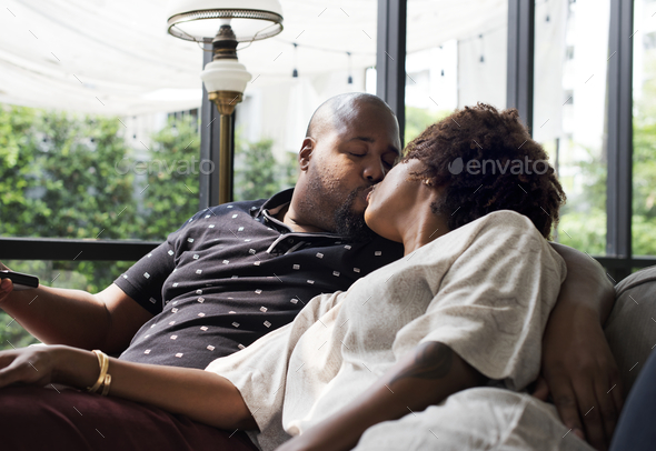 Black couple kissing on the couch - Stock Photo - Images