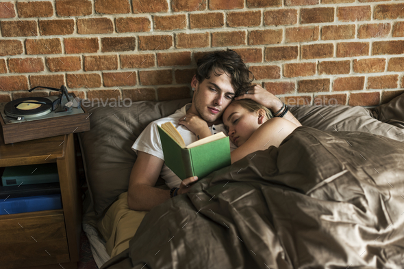 Caucasian couple spending time together in bed - Stock Photo - Images