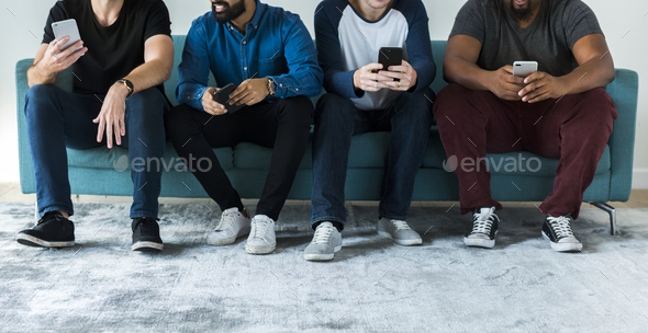 Group of diverse men using mobile phone social media and internet concept - Stock Photo - Images