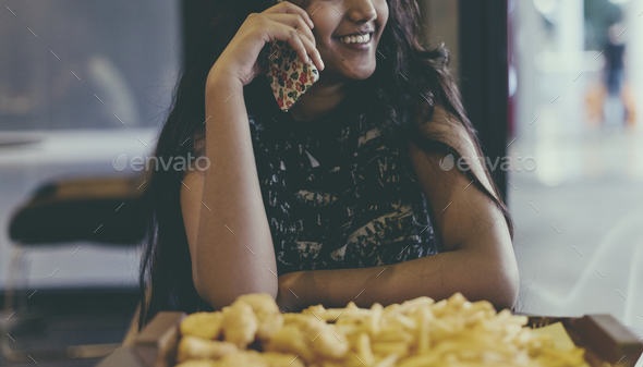 Close up of teenage girl talking on a phone eating french fries youth culture concept - Stock Photo - Images