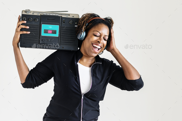 A woman listening to the music from a radio - Stock Photo - Images