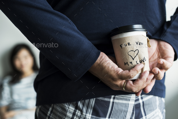 Romantic asian man brings a cup of coffee for wife - Stock Photo - Images