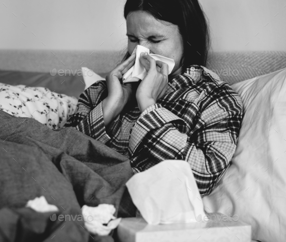 Sick woman sneezing in bed - Stock Photo - Images