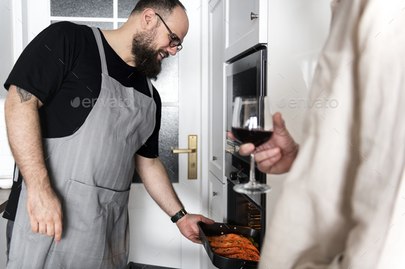 Man putting raw salmon steak into oven - Stock Photo - Images