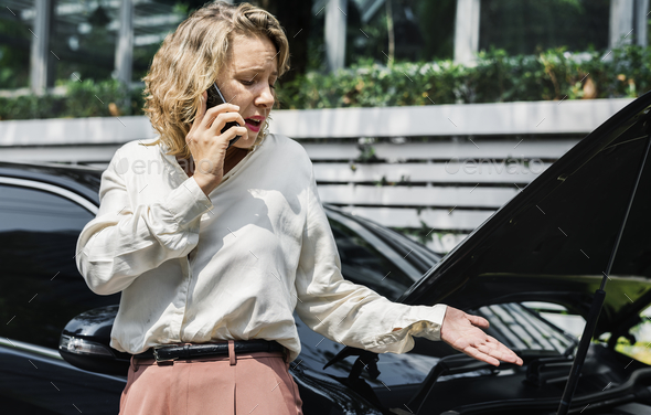 Tensed woman on call about her car - Stock Photo - Images