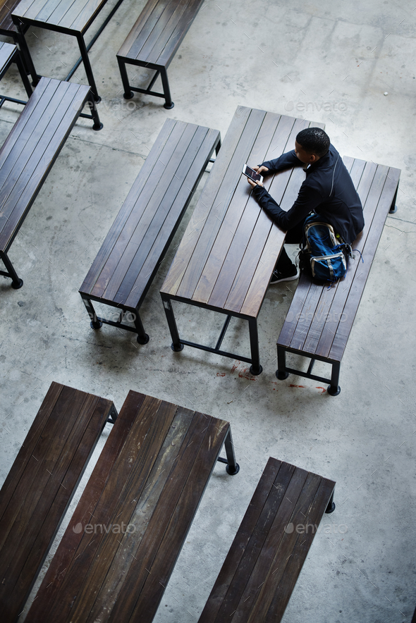 Teenage boy sitting alone in an empty canteen - Stock Photo - Images