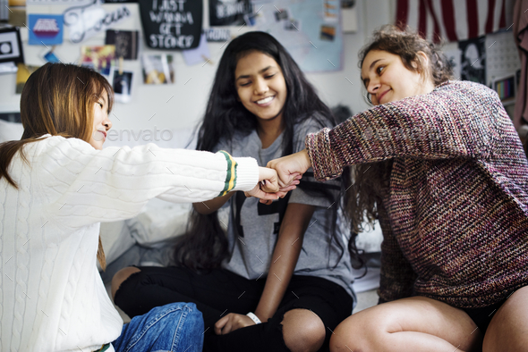 Teenage girls in a bedroom fist bumping friendship concept - Stock Photo - Images