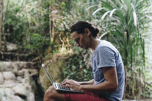 White man using computer laptop at waterfall - Stock Photo - Images