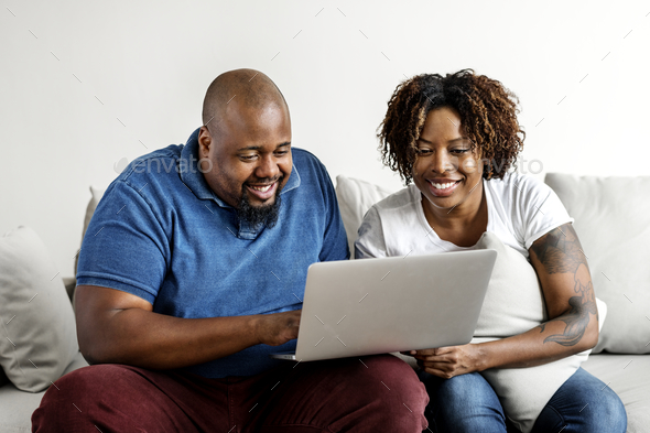 Black couple using digital device - Stock Photo - Images