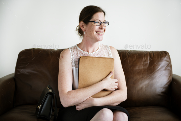 Businesswoman sitting on a couch - Stock Photo - Images