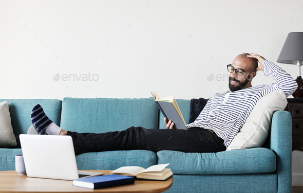 Bearded man reading on the couch - Stock Photo - Images