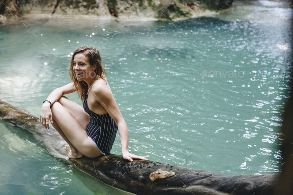 Woman sitting in a natural pond - Stock Photo - Images