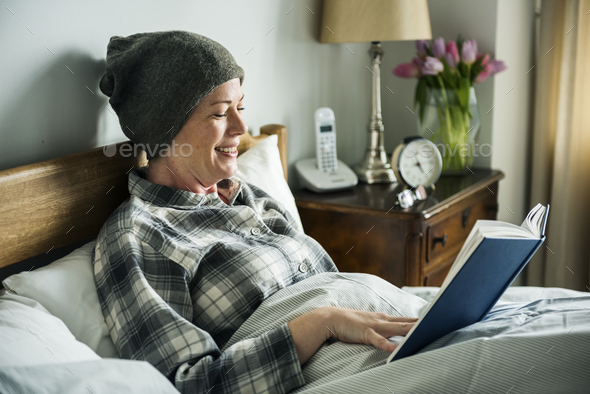 Patient reading in bed - Stock Photo - Images