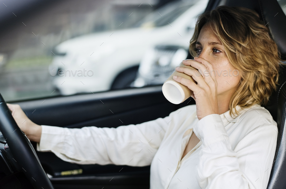 Woman drinking coffee in a car - Stock Photo - Images