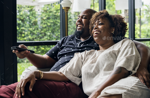 Cheerful couple watching TV together - Stock Photo - Images