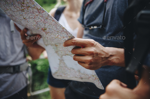 Group of friends looking at a map while hiking - Stock Photo - Images