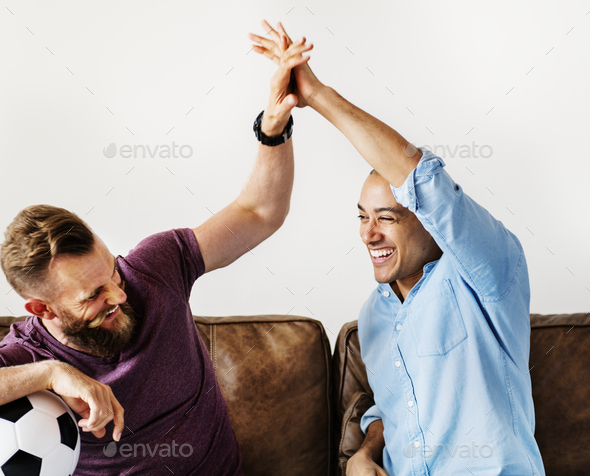 Friends cheering a game on television together - Stock Photo - Images