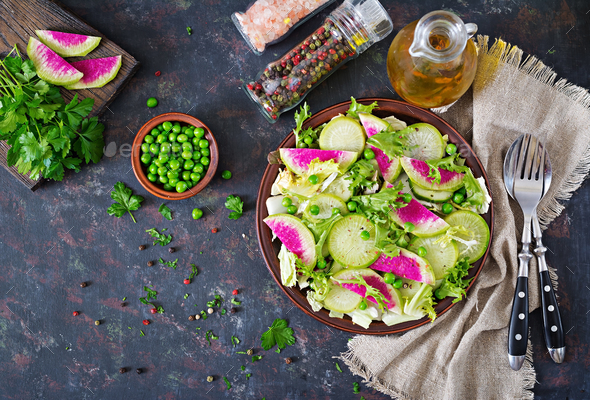 Salad from radish, cucumber and lettuce leaves. Vegan food. Dietary menu. Top view. Flat lay - Stock Photo - Images