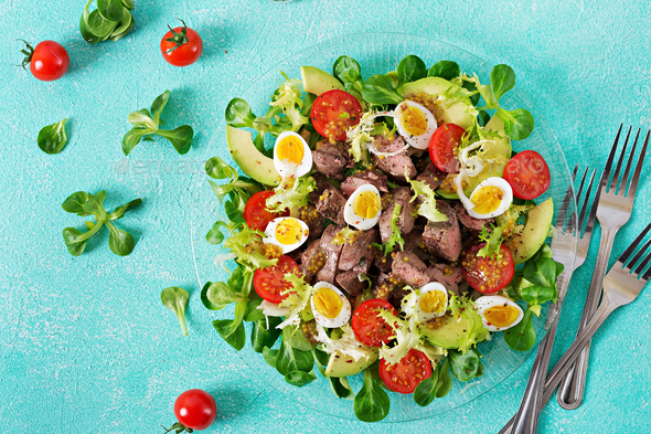 Warm salad from chicken liver, avocado, tomato and quail eggs.  - Stock Photo - Images