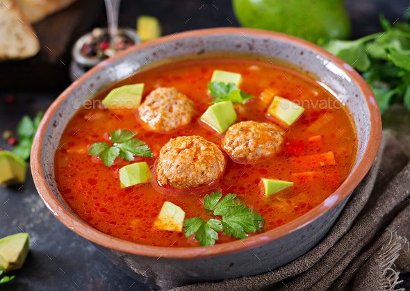 Spicy tomato soup with meatballs and vegetables. Served with avocado and parsley. Healthy dinner - Stock Photo - Images