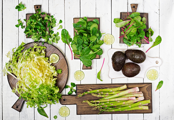 Green herbs, asparagus and black avocado on a white wooden background. Top view. Flat lay - Stock Photo - Images