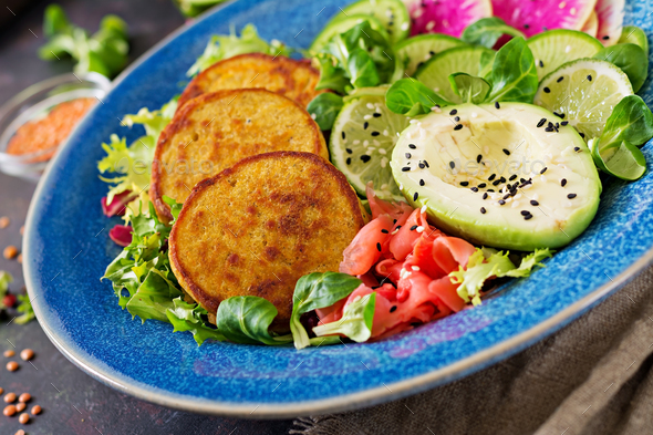 Healthy vegan lunch bowl. Fritter with lentils and radish, avocado salad - Stock Photo - Images