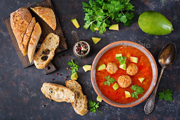 Spicy tomato soup with meatballs and vegetables. Served with avocado and parsley.  - Stock Photo - Images