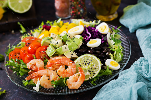 Grilled shrimps and fresh vegetable salad - avocado, tomato, black beans, red cabbage and paprika - Stock Photo - Images
