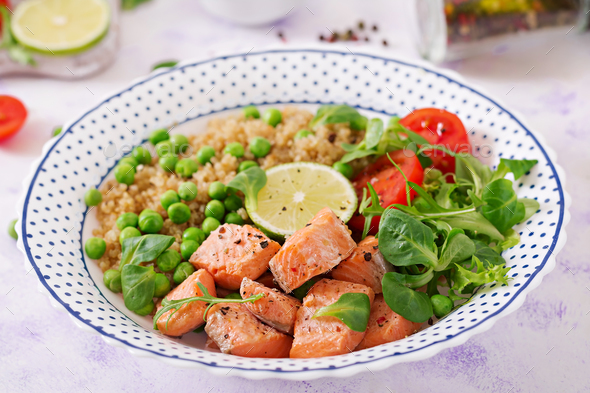 Healthy dinner. Slices of grilled salmon, quinoa, green peas, tomato, lime and lettuce leaves - Stock Photo - Images