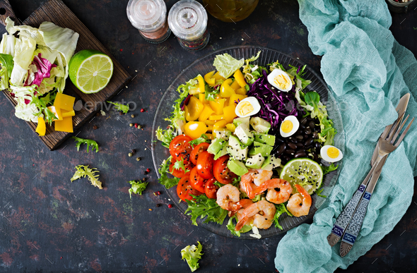 Grilled shrimps and fresh vegetable salad - avocado, tomato, black beans, red cabbage and paprika. - Stock Photo - Images