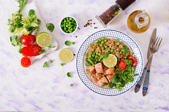 Slices of grilled salmon, quinoa, green peas, tomato, lime and lettuce leaves - Stock Photo - Images