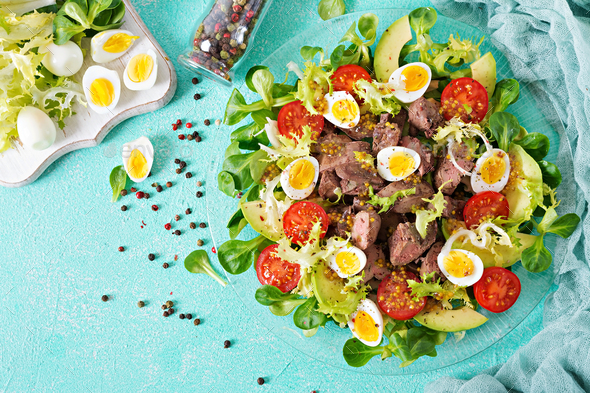 Warm salad from chicken liver, avocado, tomato and quail eggs. Healthy dinner. - Stock Photo - Images
