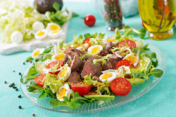 Warm salad from chicken liver, avocado, tomato and quail eggs. Healthy dinner. Dietary menu. - Stock Photo - Images