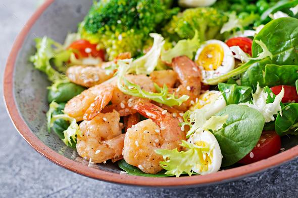 Grilled shrimps and fresh vegetable salad, egg and broccoli. Grilled prawns.  - Stock Photo - Images