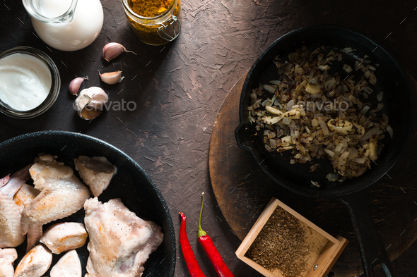 Fried chicken pieces in a frying pan, onions and chili. Indian food - Stock Photo - Images