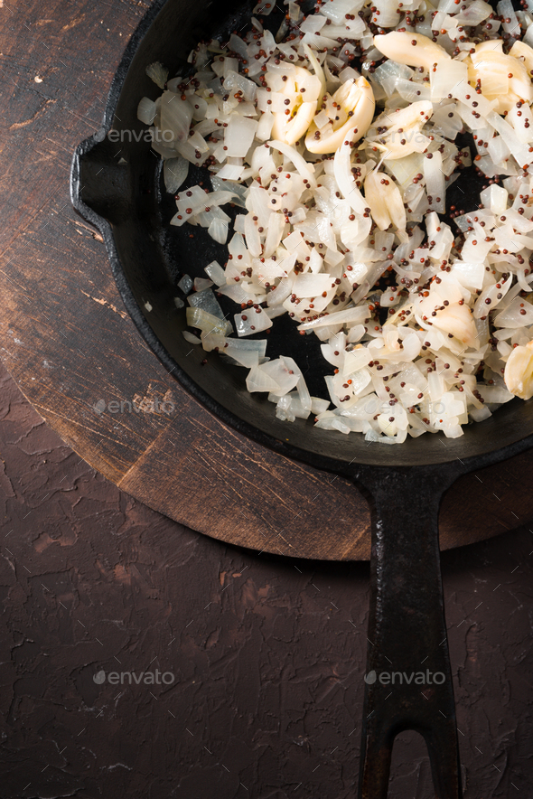 Fried onions, garlic and mustard seeds in a cast-iron frying pan free space. Indian food - Stock Photo - Images