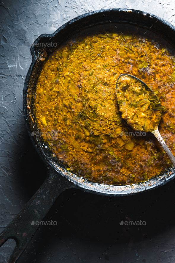 Preparation of curry paste in a cast-iron frying pan closeup. Indian food - Stock Photo - Images
