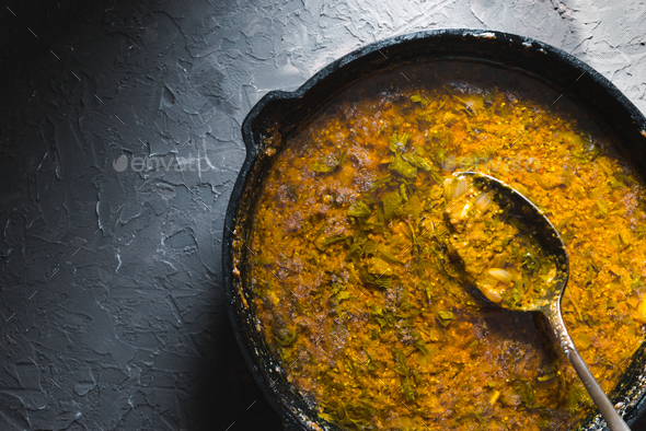 Preparation of curry paste in a cast-iron frying pan. Indian food - Stock Photo - Images