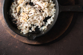 Fried onions, garlic and mustard seeds in a cast-iron frying pan. Indian food - PhotoDune Item for Sale