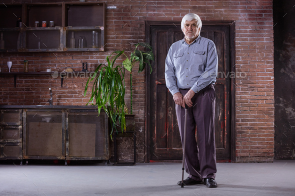 Portrait of senior man with walking stick - Stock Photo - Images