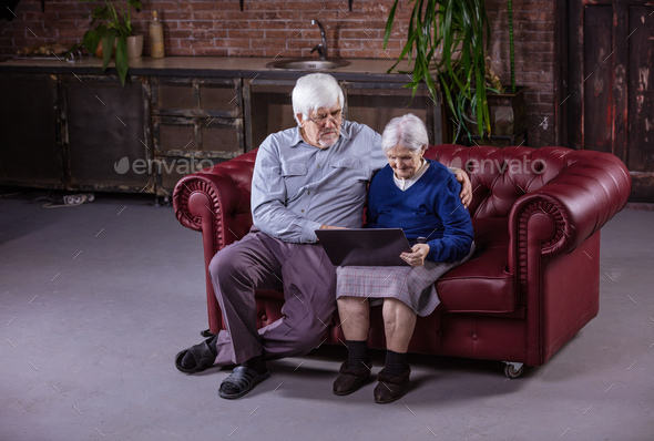 Senior couple using laptop while sitting on couch - Stock Photo - Images