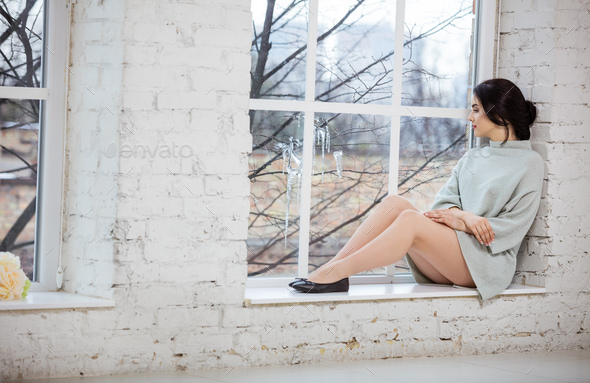 Beautiful young woman sitting by window - Stock Photo - Images