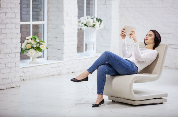 Beautiful young woman using tablet indoors - Stock Photo - Images
