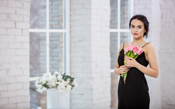 Beautiful young woman with bunch of tulips - Stock Photo - Images
