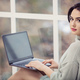 Beautiful young woman using laptop while sitting by window - PhotoDune Item for Sale