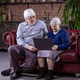 Senior couple using laptop while sitting on couch - PhotoDune Item for Sale