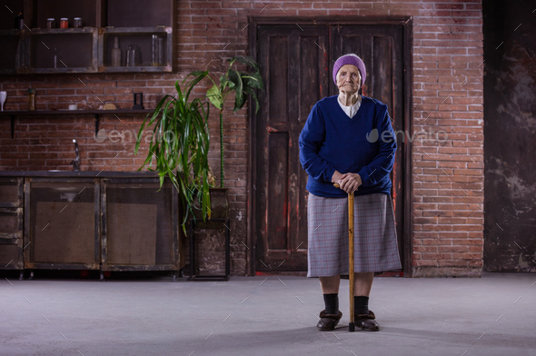 Portrait of senior woman with walking stick at home - Stock Photo - Images
