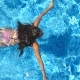 Unrecognizable Beautiful Girl Floating Across the Pool of Hotel. Young Woman Swimming in Clear Blue - VideoHive Item for Sale